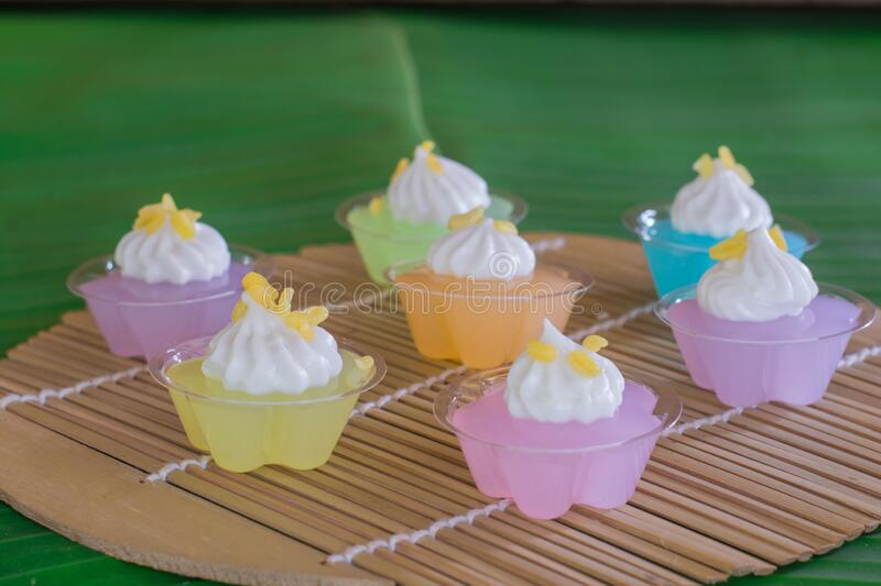 Thai sweet dessert. Group of mung bean flour and coconut cream in small plastic cup on green banana leave. Thai dessert. Group of mung bean flour and coconut stock images