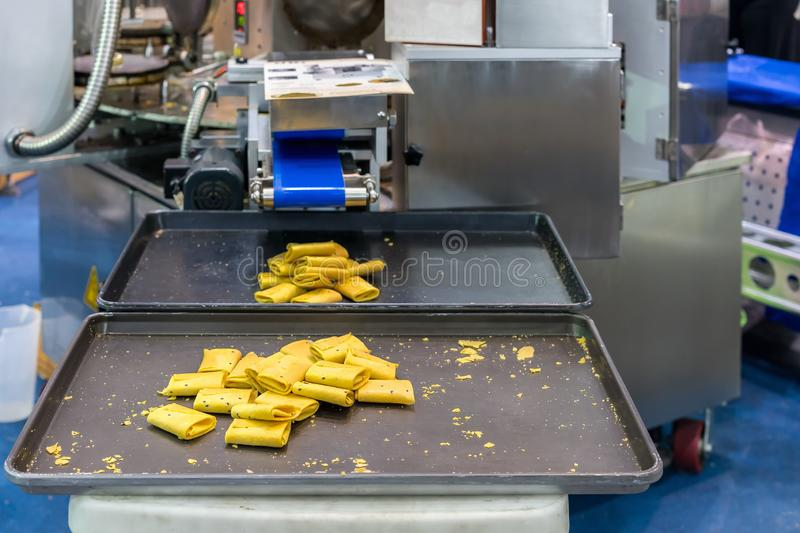 Thai dessert name tong muan or tong pup Roll or fold wafer on tray of automatic sweets making machine in production line for. High technology of industrial food stock photo