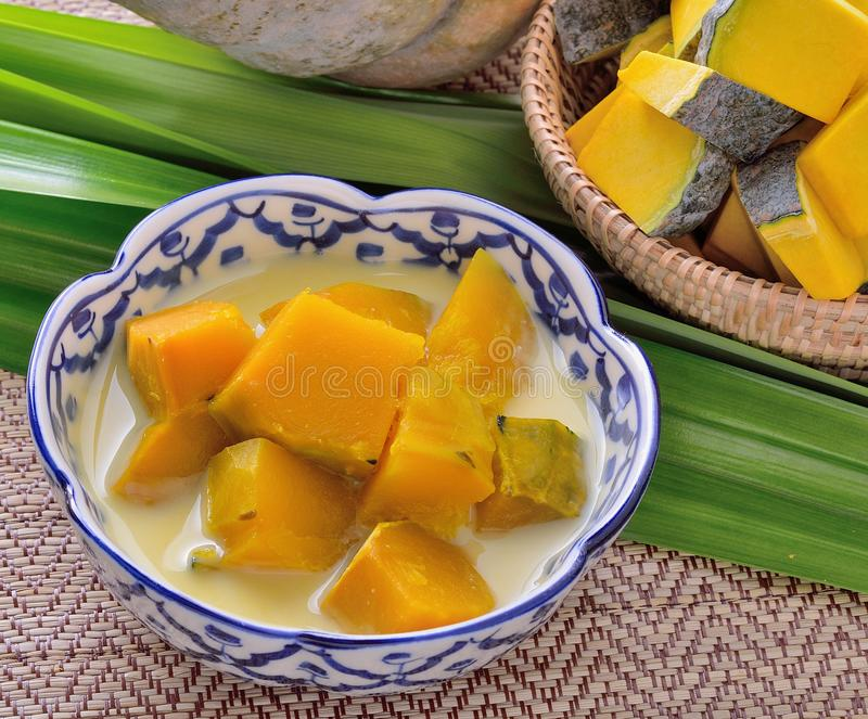 Thai Dessert, pumpkin in sweet coconut on wooden background royalty free stock images