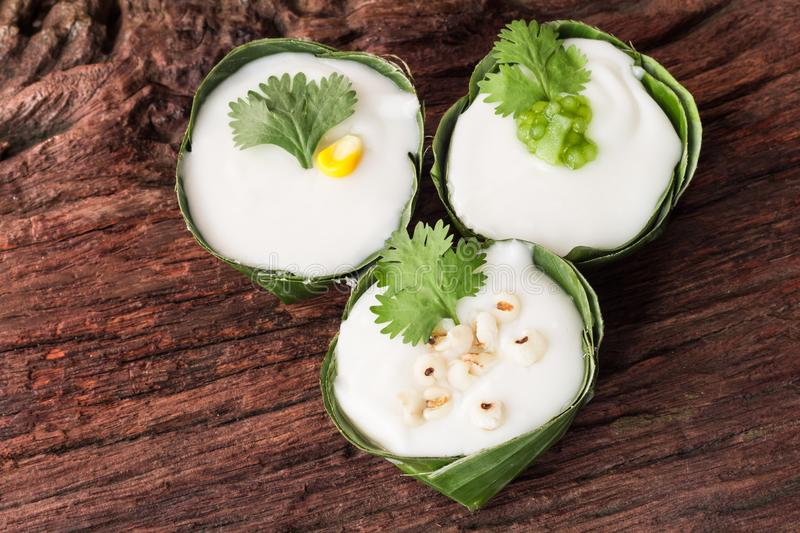 Thai dessert. Sweet pudding with Coconut, Corn, Sago, Taro, Coriander topping and wrapped with banana leaves on wooden background stock photography