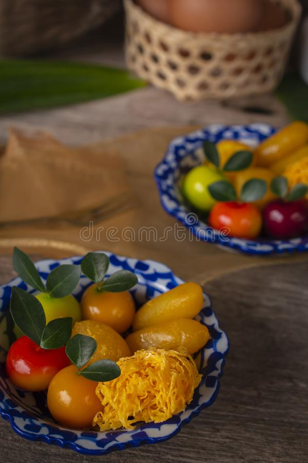 Thai desserts on a plate of white and blue stripes placed on wood table there are Similar object, fork, pandan, coconut, egg in. Basket and golden cloth placed royalty free stock photo