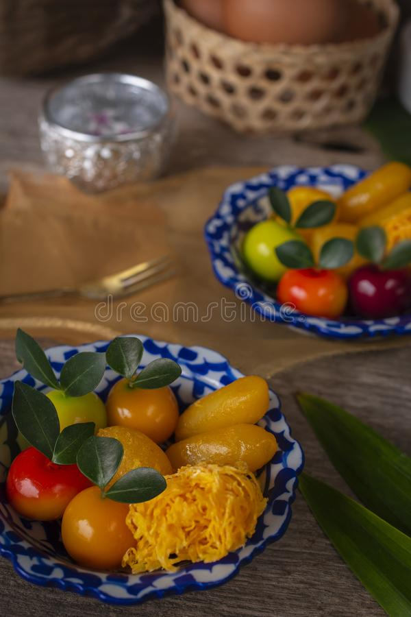 Thai desserts on a plate of white and blue stripes placed on wood table there are Similar object, fork, pandan, coconut, egg in. Basket, water bowl and golden royalty free stock photos