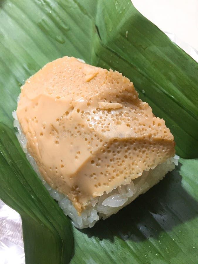 Thai desserts. Pumpkin yolks on Sticky rice in banana leaf wrap royalty free stock image