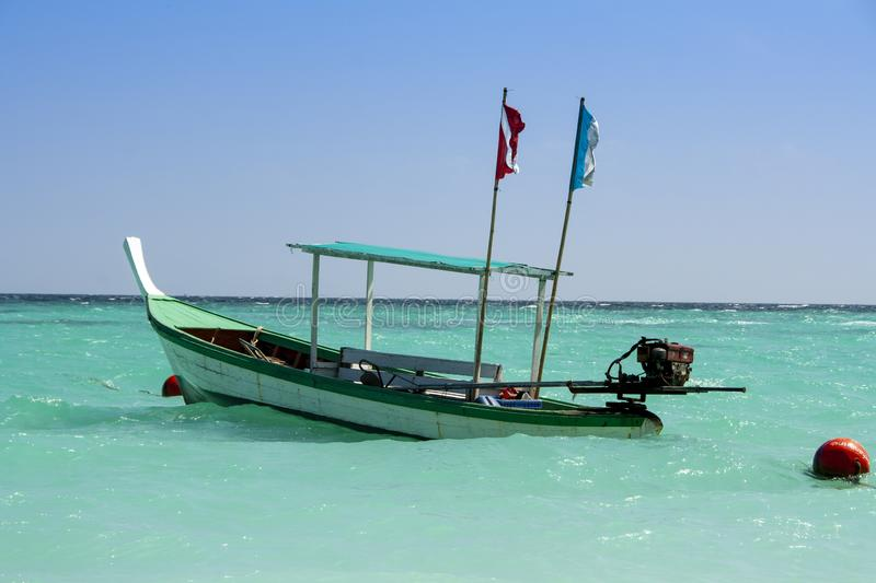 Thai diving boat in a clear blue sea. Diving boat laying in front of the beach of Koh Lipe in Thailand stock photos