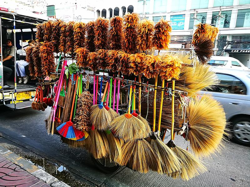 Thai dried Grass broom and Chicken Feather Dust Household Cleaning Tool Removal Brush retailer ,store them on cargo motorbike. BANGKOK, THAILAND. – On stock photos