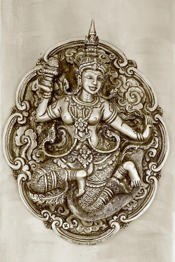 Thai fairy relief art work in sepia tone. The beautiful relief art work about Thai fairy presents on the wall of wat in Thailand stock photos