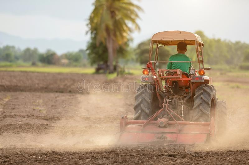 Thai farmer on big tractor in the land to prepare the soil for rice season royalty free stock photography