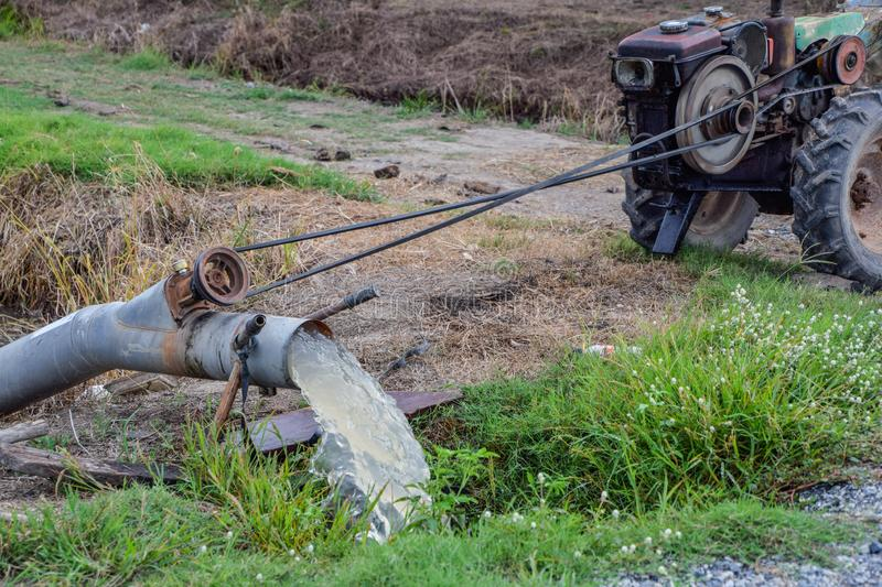 Thai farming methods - Pumping water from the canal to rice fields, Engine, baler from the canal into rice field, The water is. Black because the water in the stock photography