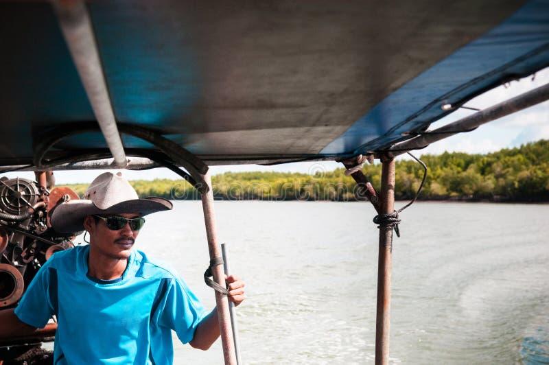 Thai fisherman drive longtail boat, Koh Lanta island, Krabi, Thailand. MAY 20, 2014 Koh Lanta, Thailand : Local Thai fisherman drive longtail boat, their part royalty free stock photography
