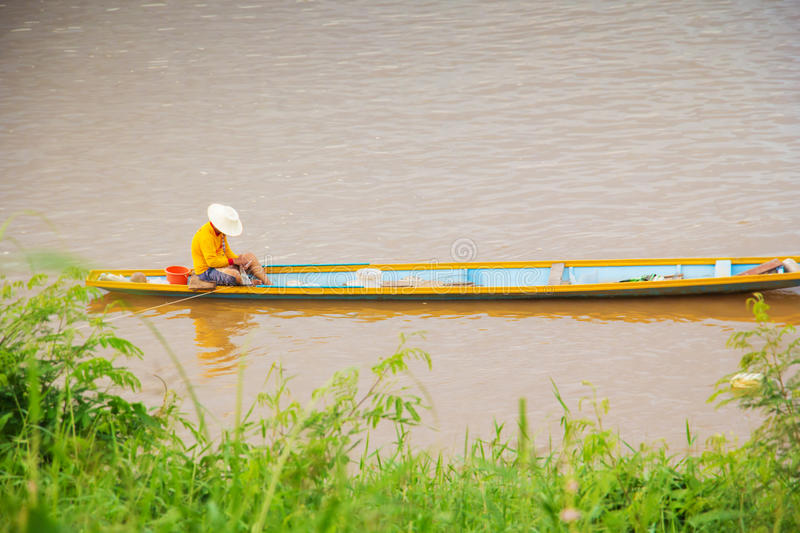 Thai fisherman on a wooden boat. In Khong river at Chiangkhan district Thailand royalty free stock image