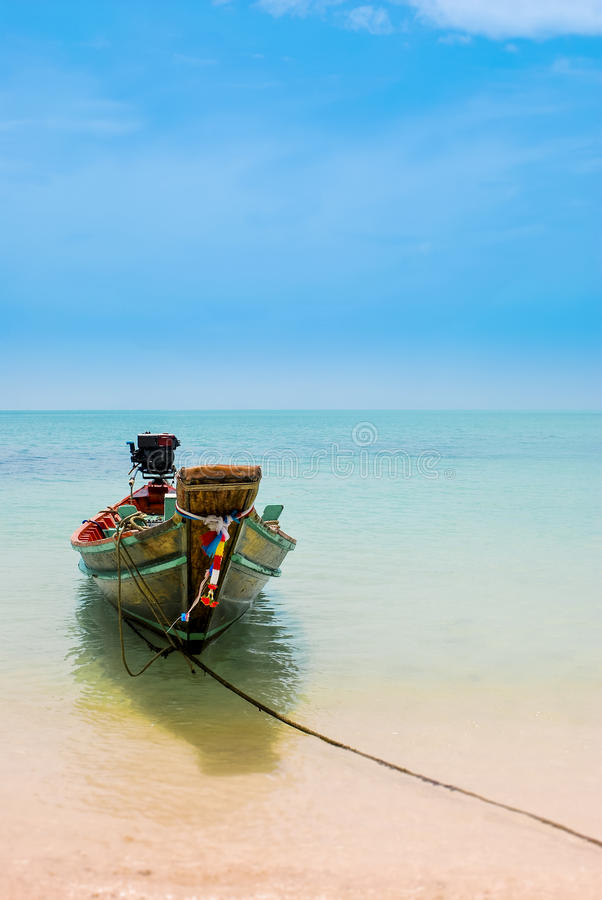 Thai fishing boat tied to a sandy beach beneath a blue sky stock image