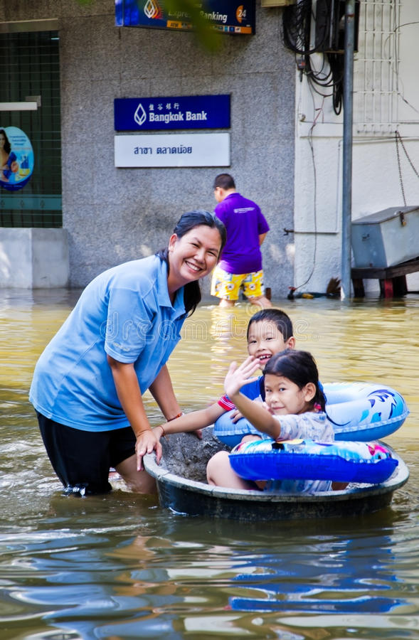 Thai flood crisis at Charoen Krung road. BANGKOK, THAILAND - OCT 29: Unidentified people use black basin as a boat to transport during the worst flooding on stock image