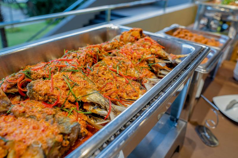 A Thai food fish stir fried in a spicy sauce in aluminum triangle plate on line buffet in front of seminar room. A Thai food fish stir fried in a spicy sauce in royalty free stock image