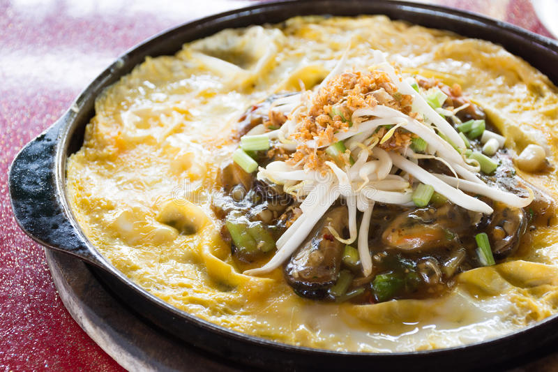 Thai food, fried mussel pancake in hot pan. Or Oysters on the hot stock photography