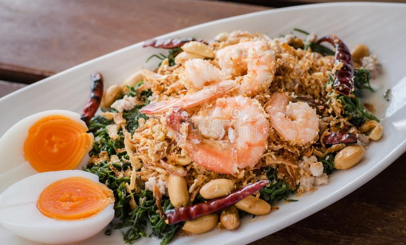 Esculentum Vegetable fern spicy salad with eggs and shrimp in coconut milk topping with peanut. Thai food name `Yum Pak Goot` is a esculentum Vegetable fern stock photos