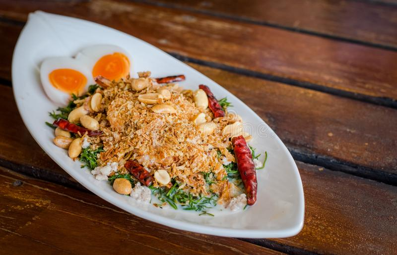 Esculentum Vegetable fern spicy salad with eggs and shrimp in coconut milk topping with peanut. Thai food name `Yum Pak Goot` is a esculentum Vegetable fern stock images
