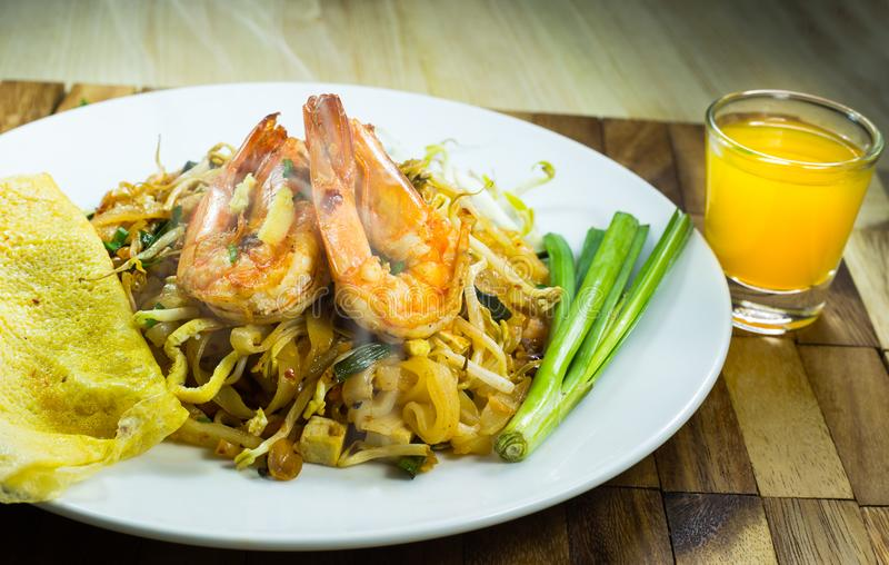 Thai food noodle and shrimp. With orange juice on wood,PAD THAI style food with smoke on food on table royalty free stock photos