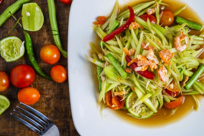 Thai food, papaya salad and tomatoes, peppers and condiments on a wooden table stock photos