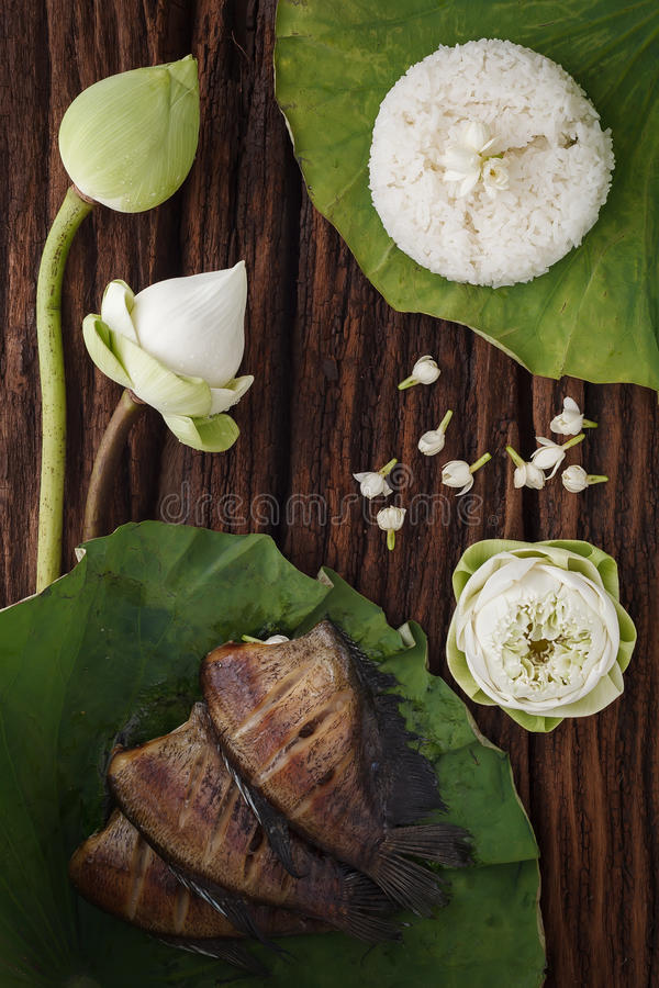 Thai food rice and dried salted damsel fish fried with flower lotus jasmine decoration on wooden background. Beautiful flat lay still life rustic asia stock photos