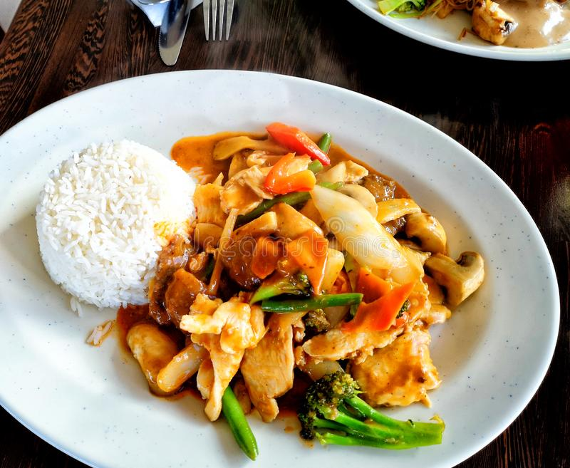 Thai Food with rice, vegtables, broccoli, red curry sauce, paprika and chicken meat. royalty free stock images