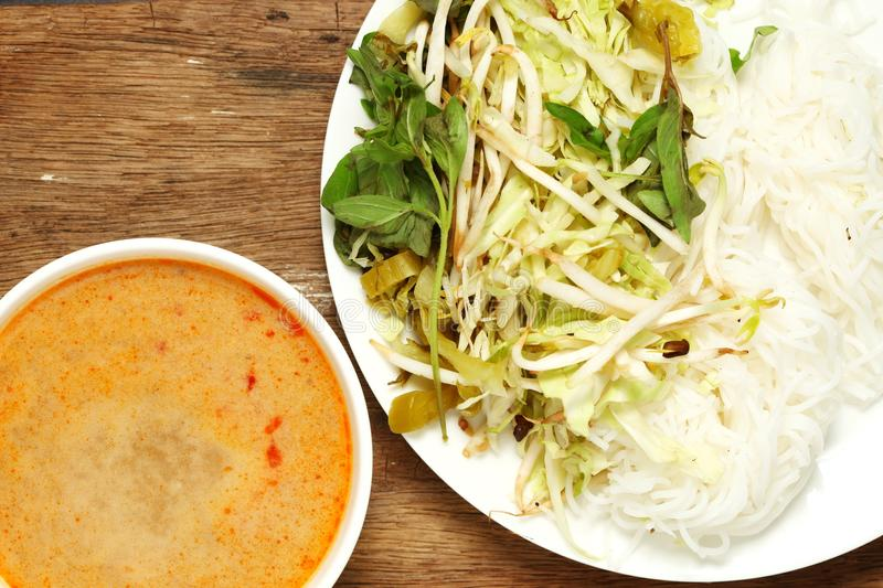Thai food scene. Thai rice flour noodles put beside bean sprouts hoary basil leaf and mustard green with spicy sauce put in the white dish represent the thai stock photos