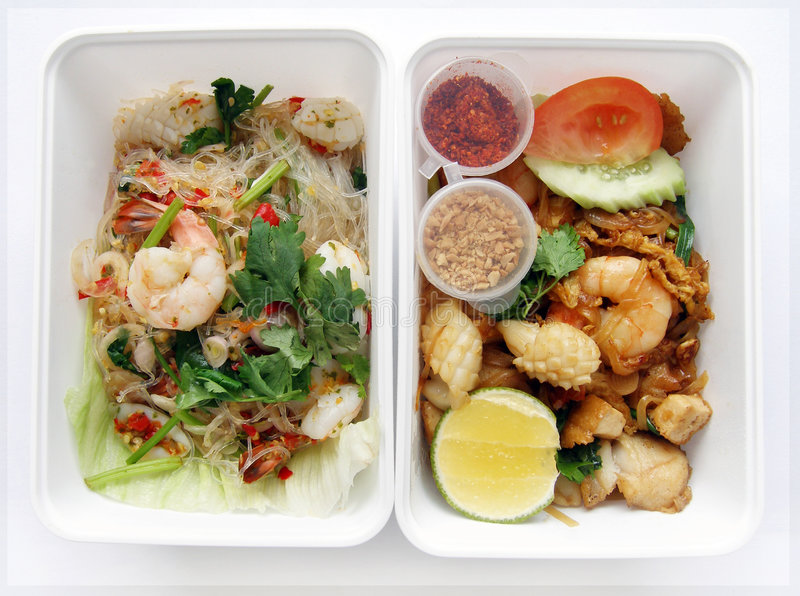 Thai food seafood salad and noodles. Thai food to go - An image of two different Thai dishes packed in takeout boxes containers. The box On the left is a seafood stock image
