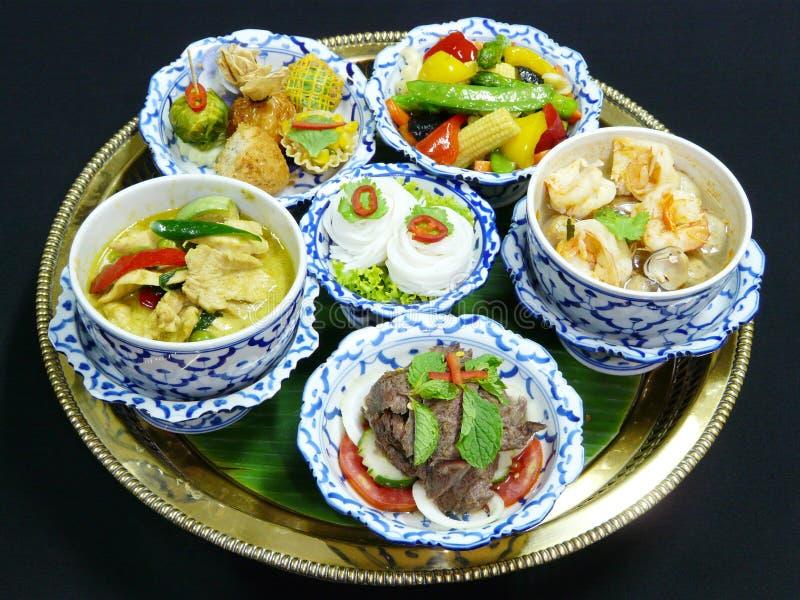 Thai food set menu. Thai mix appetizers (rhoom, kang kao peuak, toong ngern yuang, krathong-tong, kung sorn klin), thai green curry with chicken, thai grilled stock photos