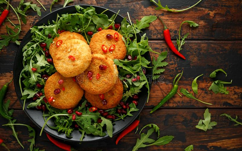 Thai food spicy fish cakes served with pomegranate seeds and wild rocket, arugula salad.  royalty free stock photography