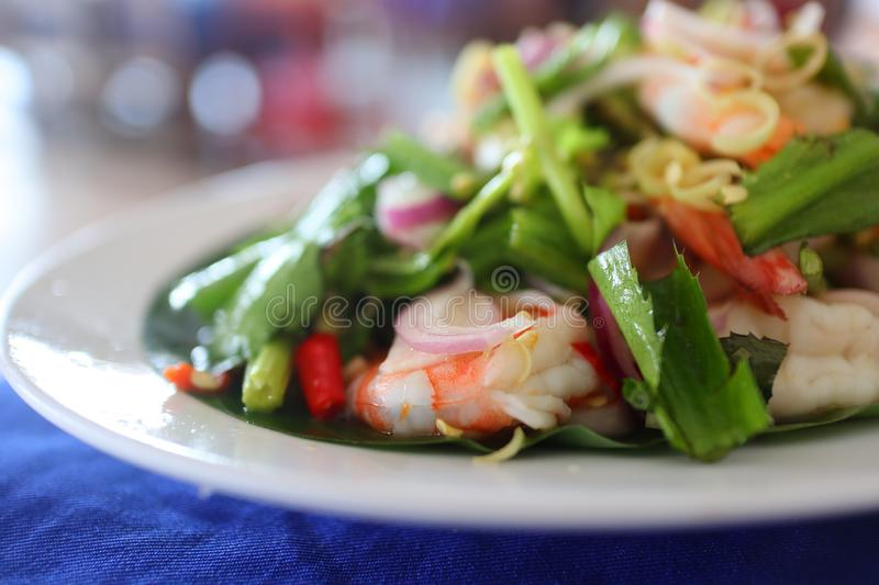 Thai food Spicy Lemongrass Salad with Shrimps. In white plate royalty free stock photo