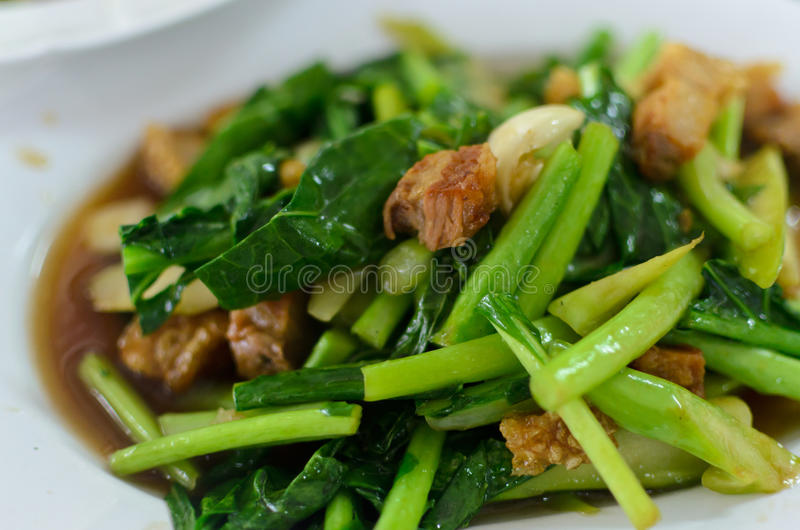 Thai food stir fried Chinese kale. With crispy pork royalty free stock images