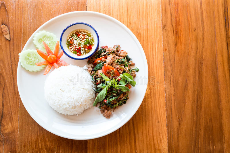 Thai food, stir fried pork with basil eating with rice. On wood table royalty free stock photography