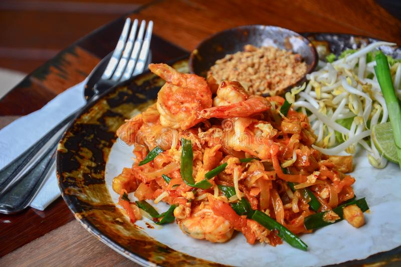Thai food, stir fry rice noodles with shrimps, tofu, vegetable and crushed peanuts or pad thai on wooden table background. Pad thai is a popular Thai street stock photography