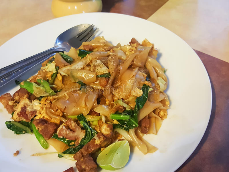 Thai food style:Pad See EiwStir fried Flat Rice Noodle with So. Y Sauce and Pork,vintage tone royalty free stock photo
