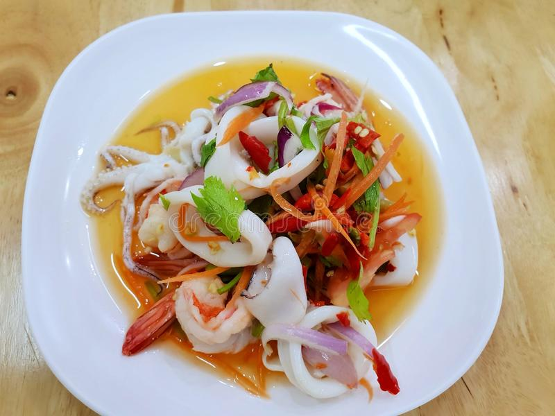 Thai food style, Top view of spicy Thai seafood salad on white plate on wooden table stock photo