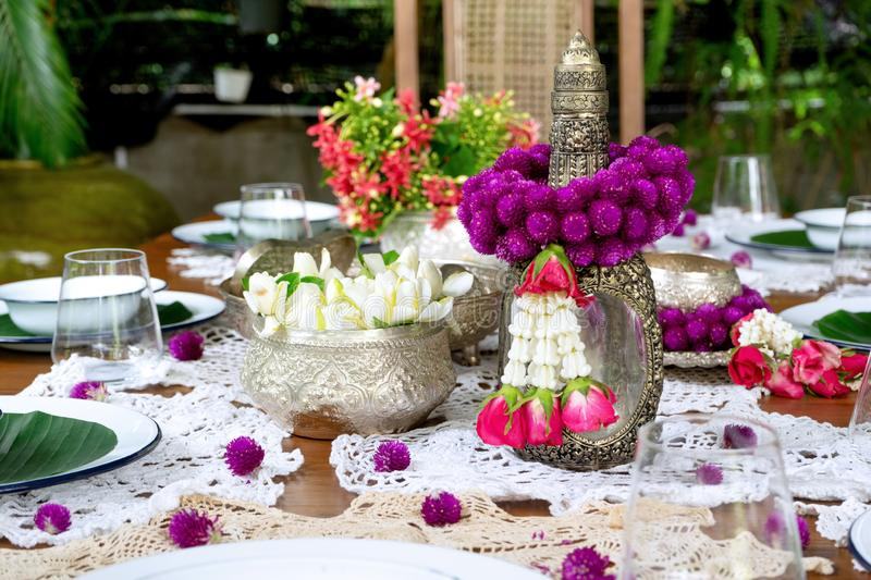 Thai food table decoration silver ware garland. Thai food table decoration silver ware flower garland, glass, restaurant, dish, plate, setting, flowers, candle royalty free stock photography