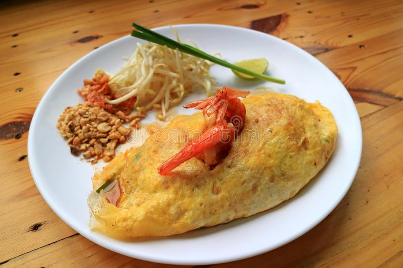 Thai Fried Noodle or Pad Thai Wrapped in Fried Egg Topped with Shrimps Served on Wooden Table royalty free stock images