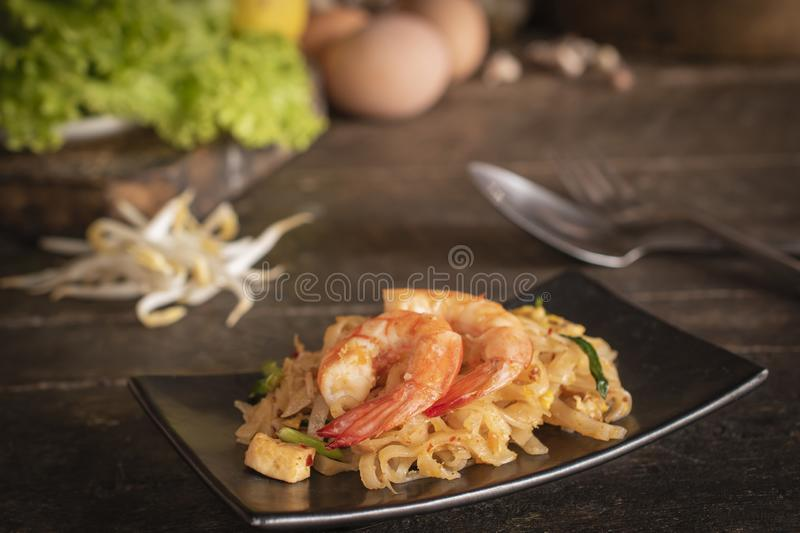 Thai fried noodles or pad thai with shrimp on black plate placed on the wood table there are fork, spoon, eggs, lettuce, garlic, royalty free stock photo