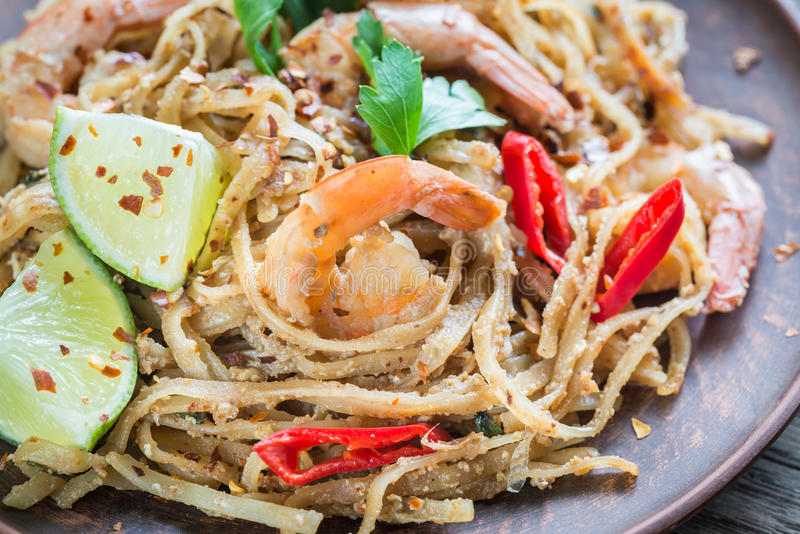 Thai fried rice noodles with shrimps. Portion of thai fried rice noodles with shrimps royalty free stock photos