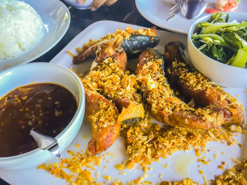 Thai fried sun dried fish with garlic and spicy sauce served in the seafood restaurant. stock image
