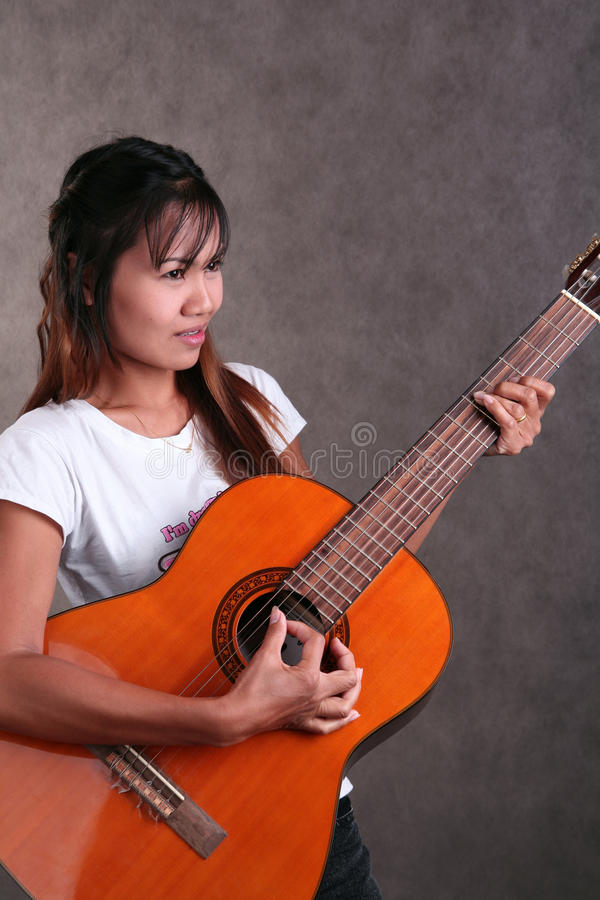 Thai girl. Playing accoustic guitar royalty free stock images
