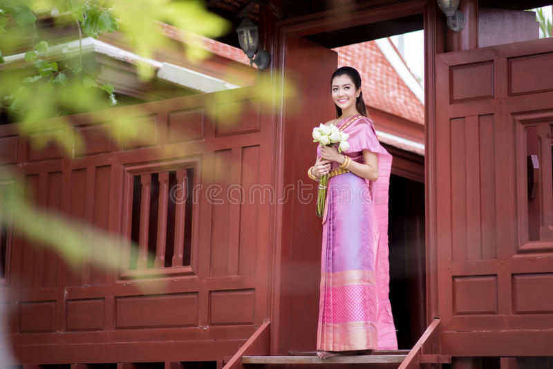 Thai girl dresses Thai traditional costume at traditional Thai royalty free stock photo