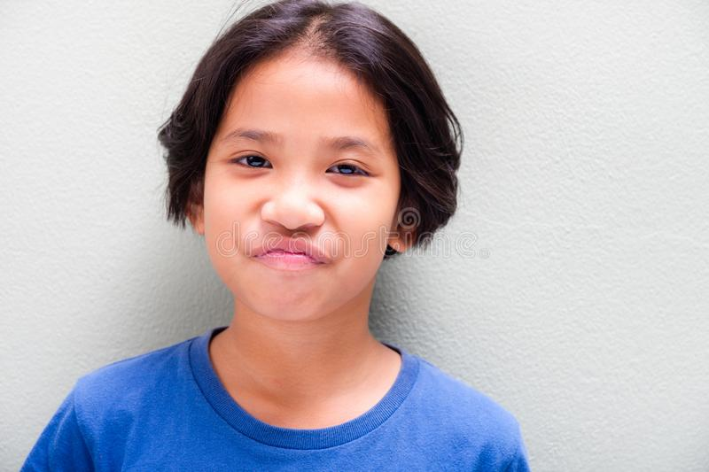 Thai Girl Express Smile Fade. Nine years old Thai girl in blue t-shirt stand at the light green wall and expresses smile fade stock photos