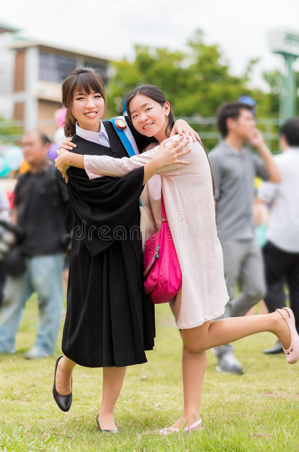 Thai girl is hugging her friend who graduated a master degree. Thai girl is hugging her friend who wear a graduation gown and graduated a master degree stock photography