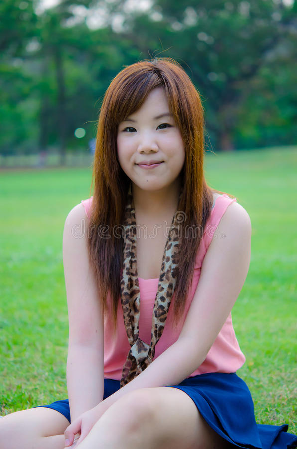 Thai girl relaxing in the park. A cute Thai girl sitting on the grass, relaxing in the park stock photography