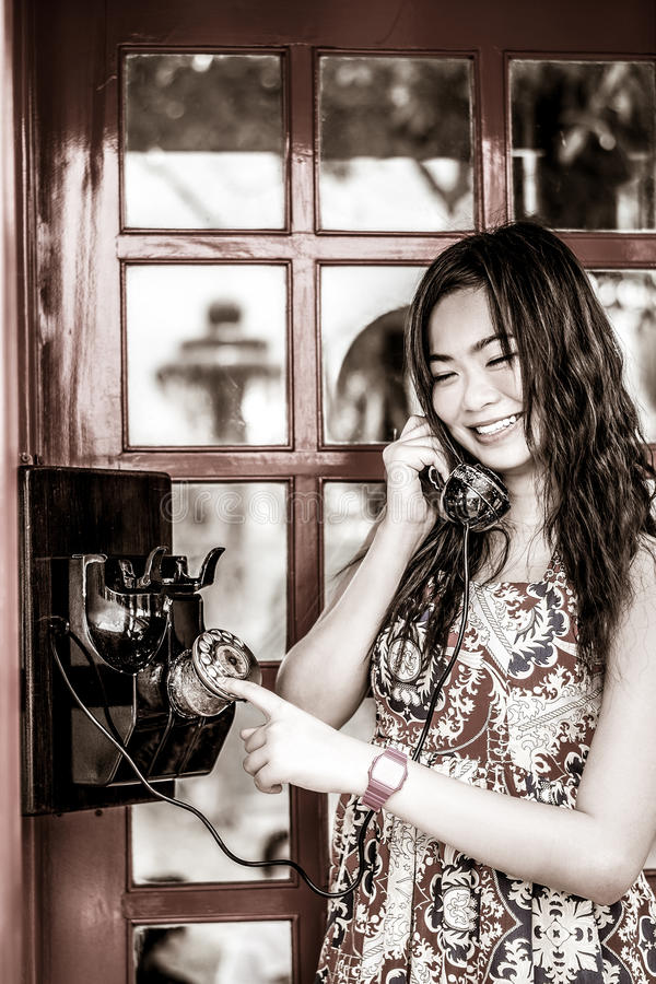 Thai girl is talking with an old-fashion phone in black and whit royalty free stock photography