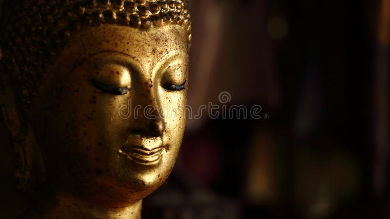 Thai golden buddha face statue close up for light side and dark side of Thailand royalty free stock photos