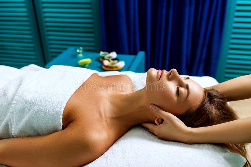 Masseuse massaging head and neck of young woman. royalty free stock image