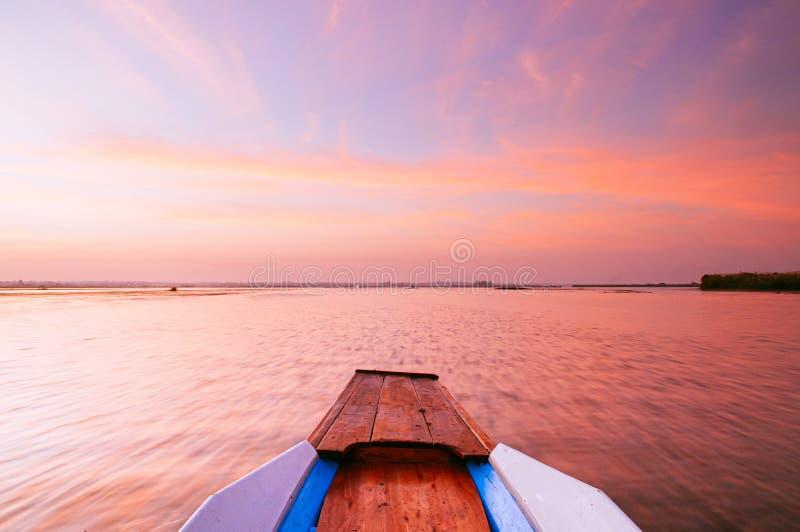 Thai houten boogboogreis in het vreedzame blauwe Nong Harn-meer - Udonthani, Thailand Het beroemde rode lotusmeer in de winter stock foto's