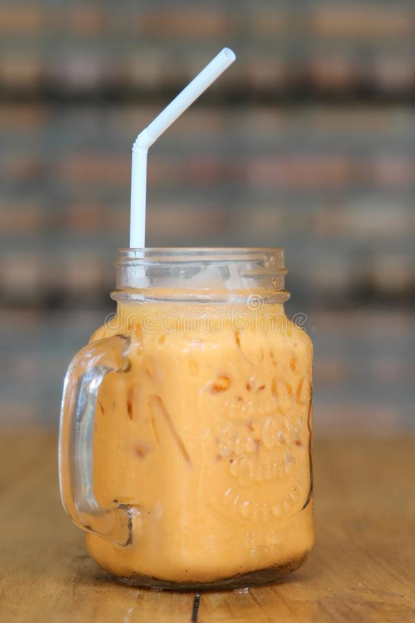 Thai ice tea. With milk in glass jar on wooden table stock photo