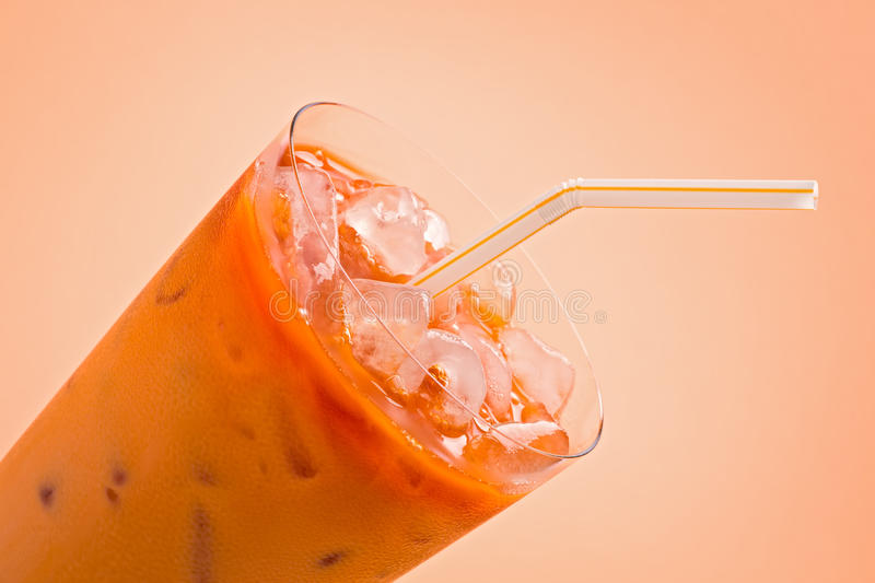 Thai Iced Tea. Glass of thai iced tea with straw against light orange background royalty free stock photos